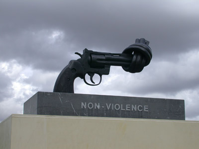Sculpture of a knotted gun with the word Non-Violence engraged on stone.