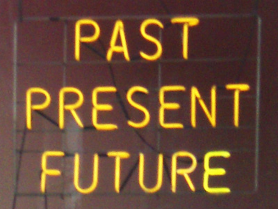 The words past, present, and future in yellow neon.