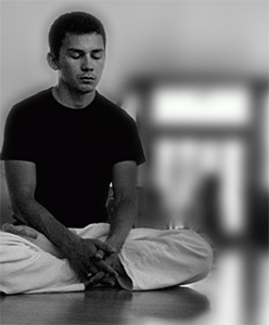 Black and white image of a young man meditating.