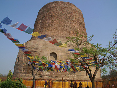 The Dhamek Stupa under clear blue sky with Tibetan prayer flags in front.