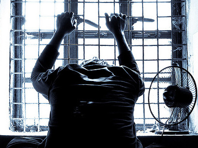 Silhouette of man holding prison bars.