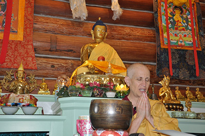 Venerable Thubten Chodron sitting in front of altar, in prayer.