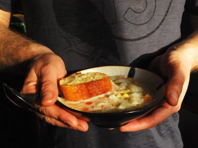 A man holding a bowl of corn soup with a small piece of bread.