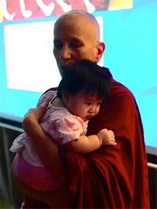 Venerable Chodron holding a baby.