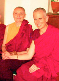 Venerable Chodron and Venerable Tenzin Palmo, holding hands and smiling.