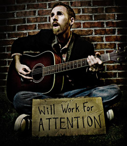 A man sitting on grass playiing a guitar, there's a card with the words: Will work for ATTENTION in front of him.
