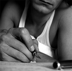 Black and white image of a man writing a letter.