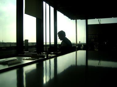 Un hombre trabajando en una oficina, frente a una ventana.