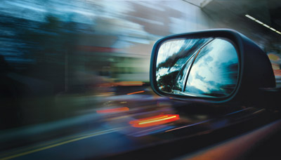 Side view mirror, car speeding down the road.