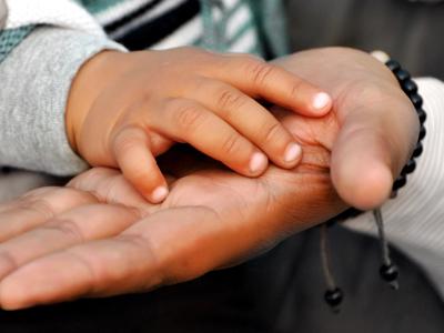 Las manos de un hijo y un padre tocándose.
