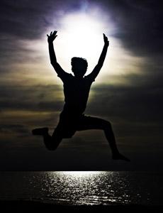 A boy jumping very high up at a beach.