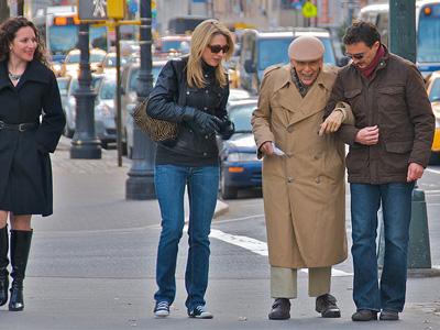 Un joven ayudando a una persona mayor a cruzar la calle.