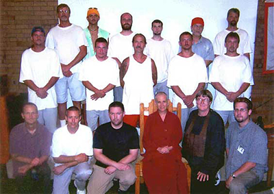 Venerable Chodron  standing with a group of inmates.