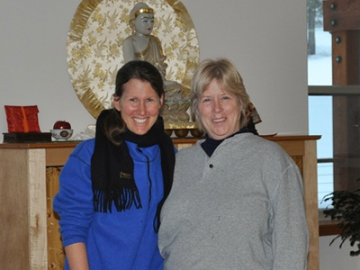 Heather with fellow retreatant, Cindy, in front of the Chenrezig Hall altar.