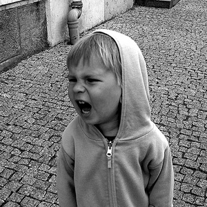 A young boy with mouth open wide, yelling