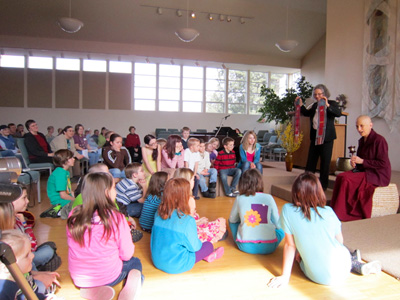 Venerable Chodron shares the story of the prayer wheel with the children at UU.