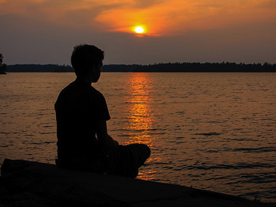 Silhouette of woman meditating by a lake, with sun setting in background.