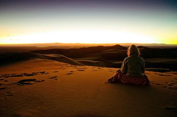 Una mujer sentada en la cima de la duna más alta, al atardecer.