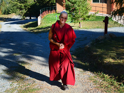 Venerable Jampa walking outside and smiling.