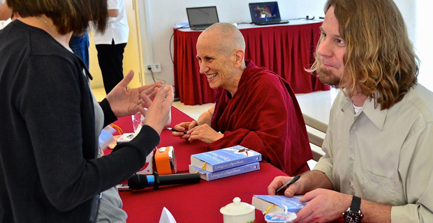 Venerable Chodron and Russell Kolts signing books.