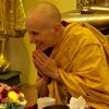 Venerable Thubten Chodron bowing forward and smiling happily.