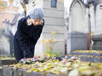 text: Người phụ nữ đặt hoa ở
