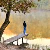 Man standing on dock of lake.