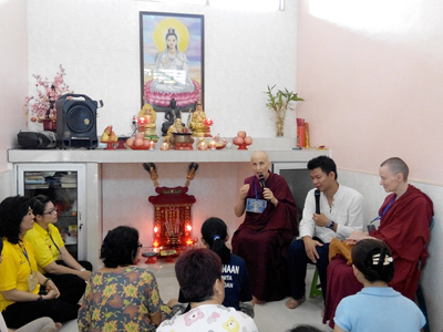 Venerable Chodron and Venerable Samten sitting with a group of inmates in the Medan prison chapel.