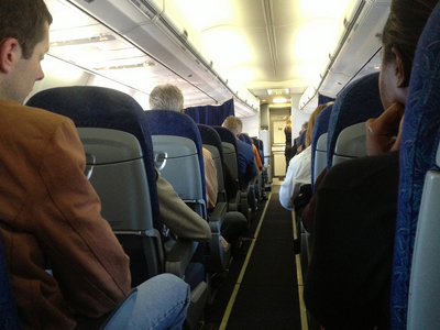 Passengers seated in an airplane cabin.