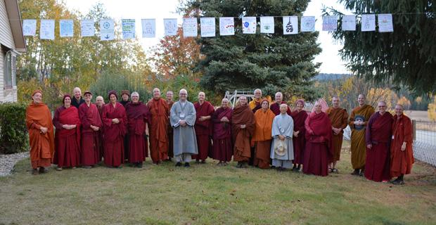 Group of monastics standing under prayer flags.