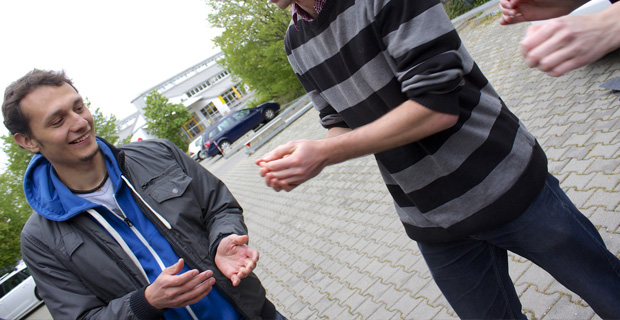 Two young men passing a hot potato.