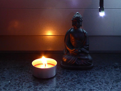 Candle by a Buddha statue.