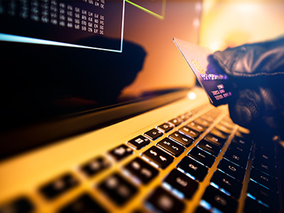 Gloved hand holding credit card at keyboard of computer.