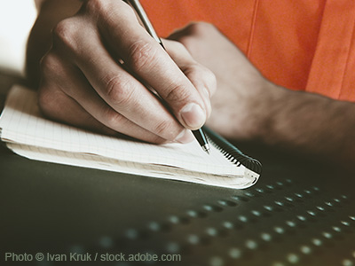 Man writing in a notebook.