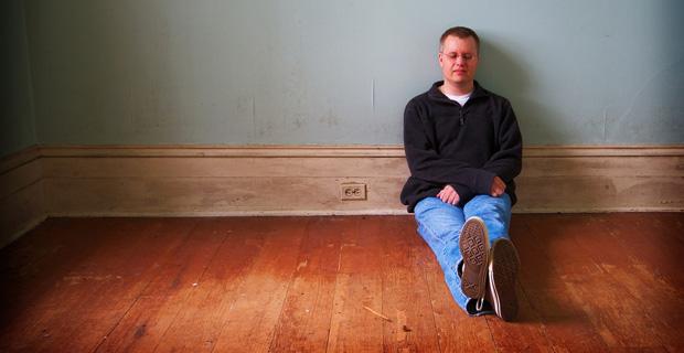Man sitting on floor, looking sad.