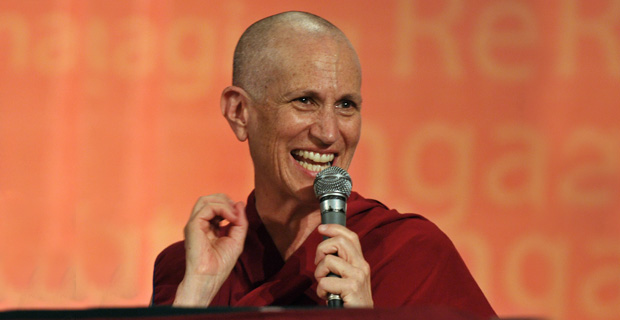 Venerable holding a microphone and smiling.