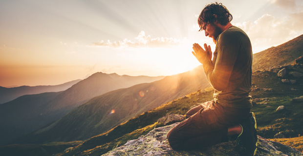Young man praying at sunset.