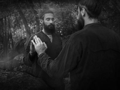 Imagem a preto e branco do homem com os olhos fechados, tocando o reflexo no espelho.