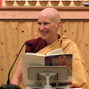 Venerable smiling while teaching behind an open book.