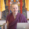 Venerable Sangye Khadro smiling while teaching in front of a thangka.